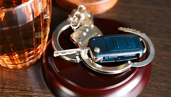 keys on handcuffs with drink in background