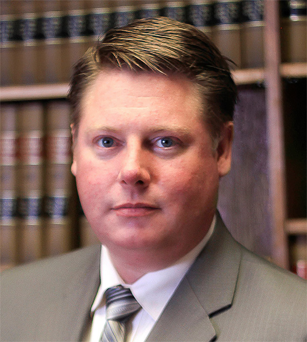 Blair W. Nelson - Criminal Defense Attorney with law books in background